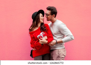 Valentin's day. Happy  beautiful couple loves each other. Handsome man with his wife posing on pink background.
