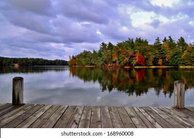 A Day At the Lake. Dock overlooking a lake with an island ablaze in autumn color. Ludington State Park. Ludington, Michigan.