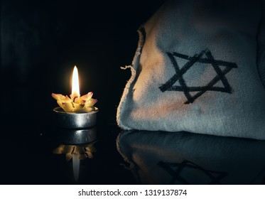 day of memory of victims of the Holocaust burning in the night candle and a symbol of the Jewish star of David