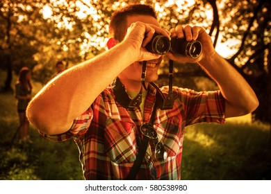 Day in nature.Guy in red shirt using binoculars. His friends are in background standing and talking.