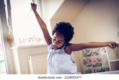 Day for new obligation. African American little girl sitting and stretching in bed. Space for copy. Close up.