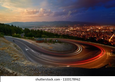 Day and Night. Light streaks over road and Skopje city in distance, Macedonia. Photo manipulation.