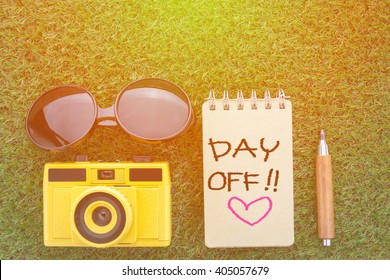 day off concept with sun glasses notebook camera and sharp pencil on grass texture view from top
