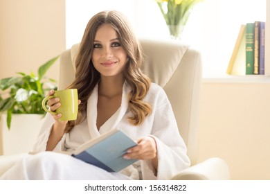 Day off at home. Attractive young woman in bathrobe drinking coffee and reading book