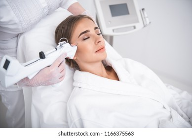 Day off at spa. Smiling girl with closed eyes lying on daybed while having beauty procedure. Cosmetologist hand in sterile glove holding automatic syringe gun