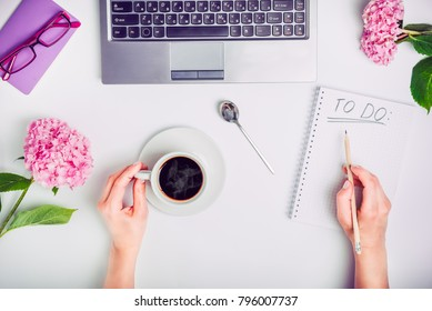 Day Planning - female hands with cup of coffee and pencil write To do list on the white working office desk with laptop, notebook, glasses, and wisteria flowers. Freelance