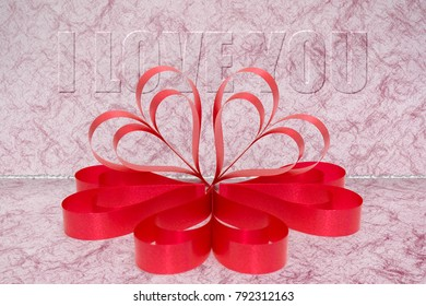 A Valentineâ??s Day red ribbons of love with pink faded background.