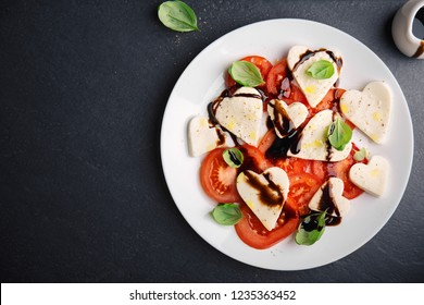 Valentine's Day salad. Italian classic caprese salad with heart formed mozzarella, basil, balsamico and tomatoes served on plate. Above view. Copy space.