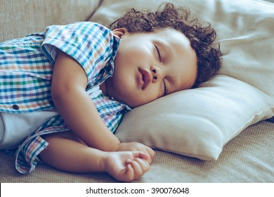 Day sleeping. Little African baby boy sleeping while lying on couch at home