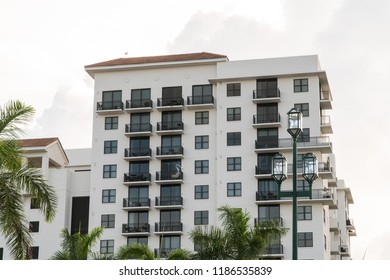 Day time exterior establishing shot of generic apartment, hotel, or condo building in tropical vacation destination location during summer time weather. Palm trees and light post in foreground