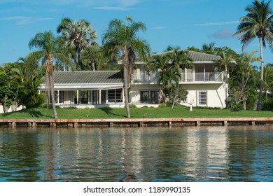 Day time exterior establishing shot of generic mansion along river in tropical island location. Palm trees and calm water in backyard of luxury home in beautiful summer destination