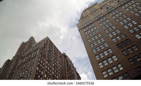 Day time exterior establishing shot looking straight up vertical at generic office apartment buildings in midtown manhattan towards the sky