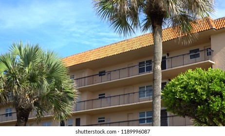 Day time exterior of generic apartment or condominium building facade on beautiful summer day in tropical geographic location. Palm trees outside of motel room entrances
