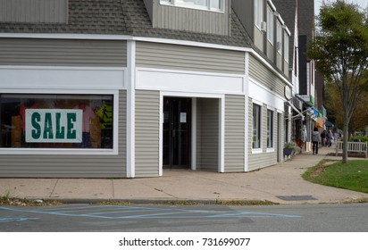 Day time exterior generic no signage retail clothing storefront on a main street in small town anywhere USA. People window shop up and down sidewalk