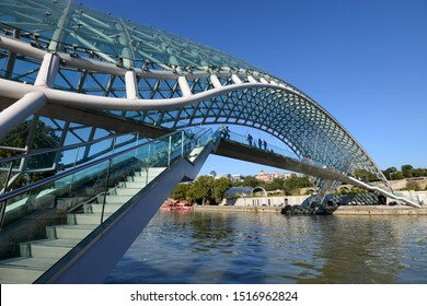 Day time view of the beautiful Bridge of Peace, a pedestrian bridge constructed in 2016 over Kura River in downtown Tbilisi, capital of Georgia. Built with steel and blue glass. No clouds. - Shutterstock ID 1516962824