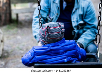 A day of vacation in the Mercadante forest, in the Puglia region of southern Italy. A child on a swing dressed in a hat and a blue down jacket plays with his grandfather.