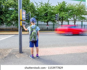 Day view little child boy with backpack pressing pedestrian signal button to cross the British road