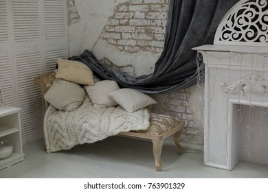 daybed with cushions in a corner of the room. wall of white brick. interior. white room with white fireplace