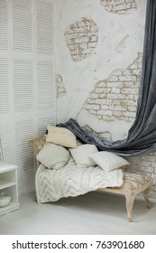 daybed with cushions in a corner of the room. wall of white brick in the room