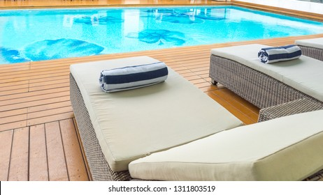 Daybed sun lounger chair poolside with towel and pool looking inviting.
