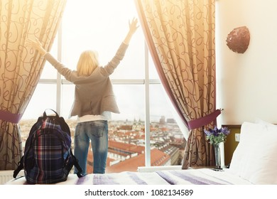 Daybreak at hotel room. Young female traveller watching cityscape, standing near big window. Happy girl with backpack ready to explore new city. Travelling and accomodation concept, copy space