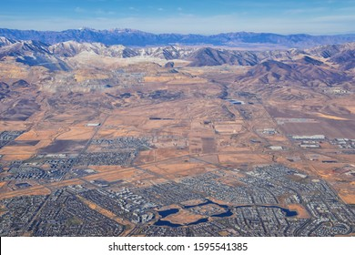 Daybreak Lake and Community and Oquirrh Mountains aerial, Copper Mine, Wasatch Front Rocky Mountains from airplane during fall. South Jordan and Herriman, Utah. United States of America. USA.
