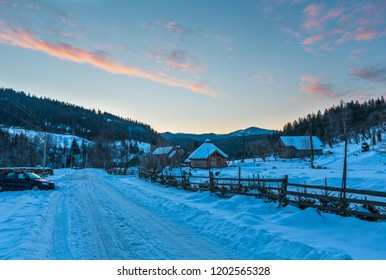Daybreak sunrise morning winter mountain village snow covered street (Ukraine, Carpathian Mountains, tranquility peaceful Dzembronya village).