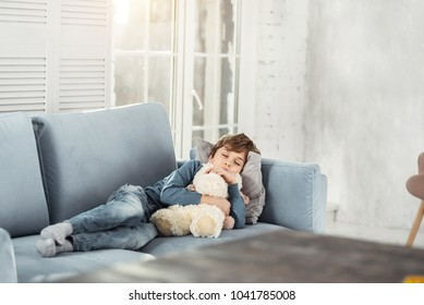 Daydream. Cute little fair-haired boy hugging his favourite nice toy and lying on the comfy sofa while taking a nap