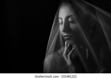 Daydreaming bride touches her chin delicately while she poses under the veil