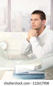 Daydreaming businessman sitting at desk in bright office.