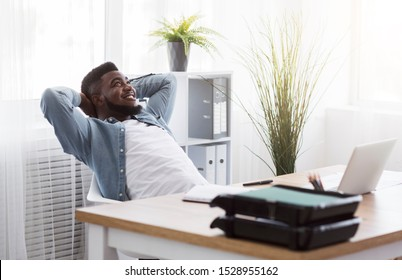 Daydreaming. Cheerful african american employee leaning back on chair with hands behind head, resting at workplace in modern office