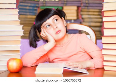 Daydreaming child girl. Schoolgirl dreaming instead learning. Bored kid in library.