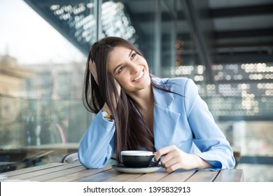 Daydreaming on a coffee break. Pensive happy woman remembering looking at side up sitting on terrace of bar coffee shop restaurant hoping thinking about future. hispanic girl wearing formal blue suit