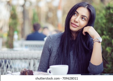 Daydreaming on a coffee break. Pensive happy woman remembering looking at side up sitting on a terrace of bar coffee shop restaurant hoping thinking of love blurred man in the green nature background