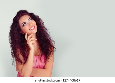 Daydreaming pensive model. Closeup portrait young hispanic latina beautiful thoughtful woman  looking up isolated on light gray green background. emotion facial expression feeling attitude