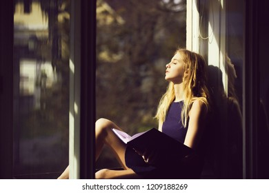 Daydreaming and relaxing. Pretty girl or young woman, student, teenager, with cute young face and blond, long hair in dress sleeping with book at open window on sill on sunny day on urban background