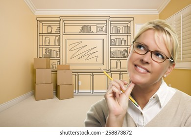 Daydreaming Woman Holding Pencil In Empty Rom with Built In Shelf Design Drawing on Wall.