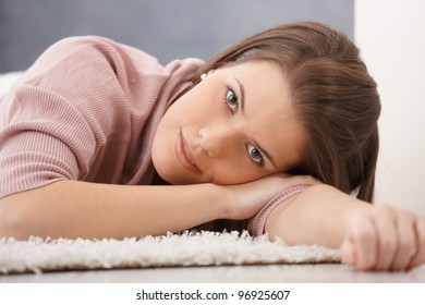 Daydreaming young woman lying on floor, smiling at camera.?