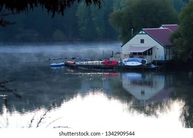 DAYLESFORD, VICTORIA, AUSTRALIA - 18 MARCH 2019: The historic boathouse on beautiful Lake Daylesford reflected in the lake's waters with early morning mist.