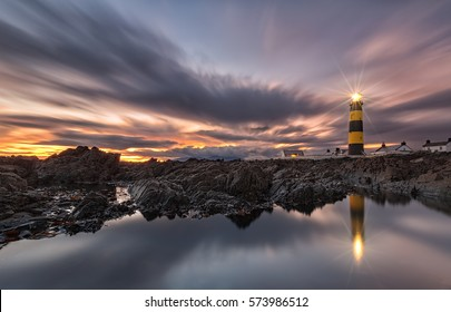 As daylight begins yielding to twilight, The St. John's Point Lighthouse at sunset  in Northern Ireland