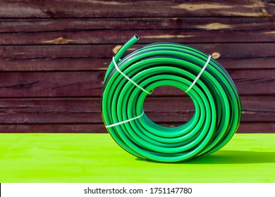daylight. bright sun. On a yellow wooden background in retro style. Rubber watering hose twisted in a bay.