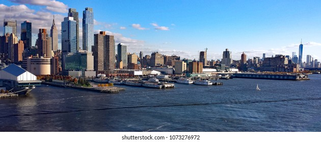 Daylight from cruise ship of the New York City skyline from mid to lower Manhattan Puffy clouds backdrop. Foreground with  port, water, tour boats, piers with urban landscaping and sailboat.