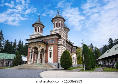 Daylight front view to Orthodox church of the Sinaia monastery in Prahova, Transylvania,  Romania. Green trees and bright blue cloudy sky on background.