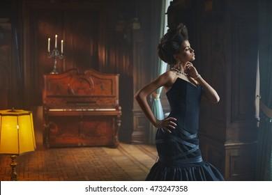 Daylight illuminates beautiful model in dark blue evening gown