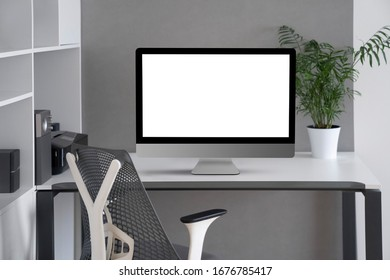 Daylight interior with white modern mock-up computer monitor on an office table, orthopaedic chair, and greenery pot on a desk, copy space. Concept of home remotely working. Home office