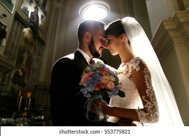 Daylight makes a halo around dreamy wedding couple standing in church