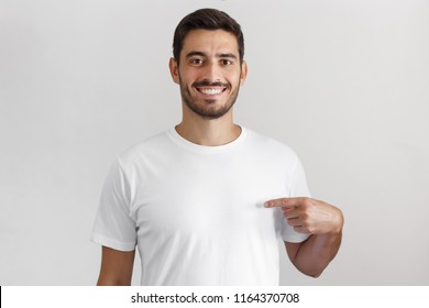 Daylight portrait of smiling nice man pointing at his blank white t-shirt with index finger, copy space for your advertising, isolated on grey background