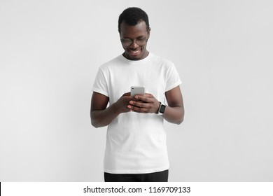 Daylight portrait of young african american man isolated on gray background wearing white t-shirt standing in front of camera, looking attentively with smile at screen of smartphone he is holding