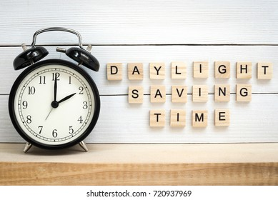Daylight Saving Time - Black Vintage Alarm Clock and Wooden Letters on White Painted Planks Background
