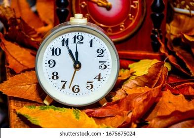 Daylight saving time. Retro styled photo. Vintage black alarm clock on autumn leaves. Time change abstract photo. Daylight saving time (DST)